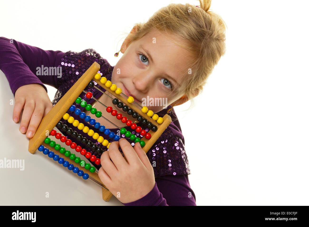 A small school child counts on an abacus., Ein kleines Schulkind rechnet mit einem Abakus. Stock Photo