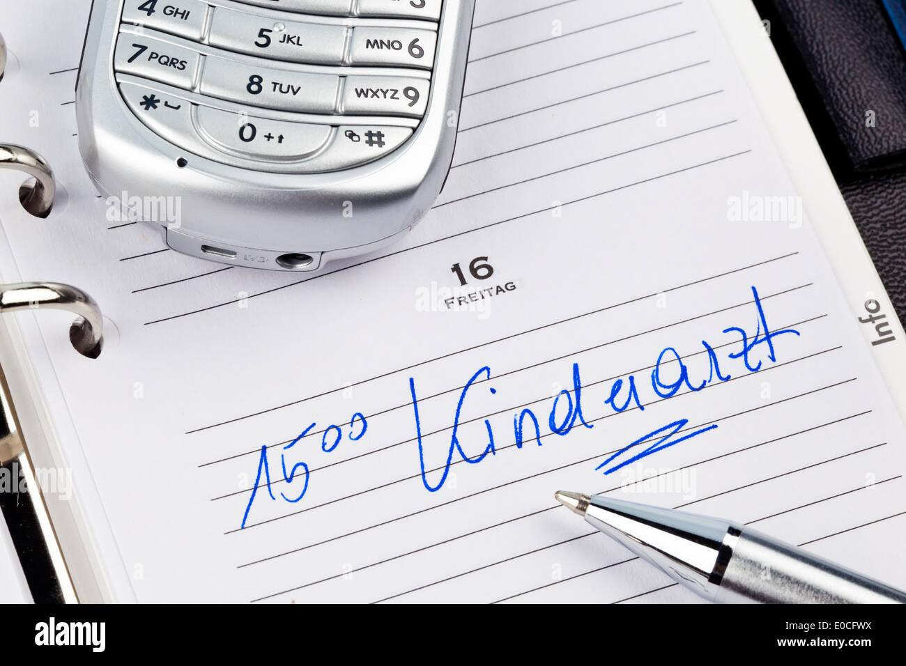 An appointment is put down in a calendar: Paediatrician, Ein Termin ist in einem Kalender eingetragen: Kinderarzt Stock Photo
