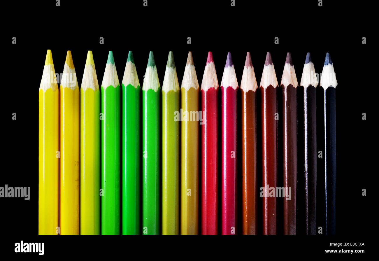Color Pencil Crayons with autumn colors ordered in chromatic scale, on black background - Stock Image
