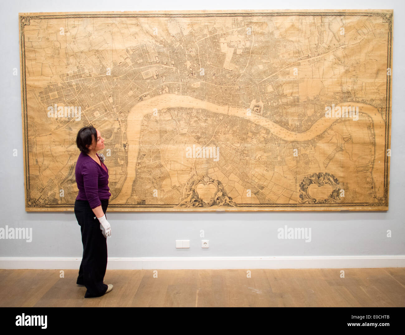 Museum employees hang a map of London