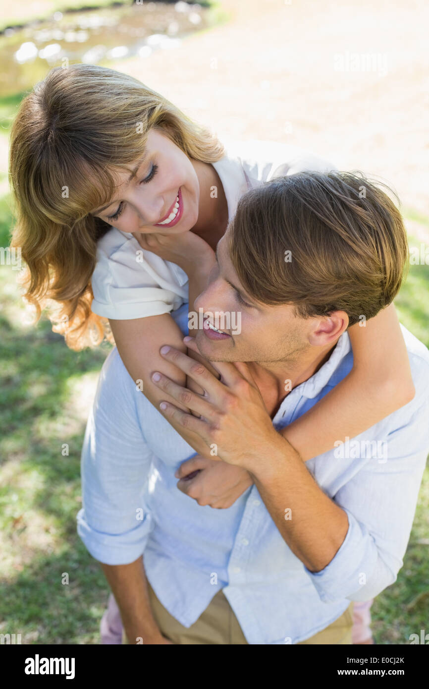 Man giving his pretty girlfriend a piggy back in the park smiling at each other - Stock Image