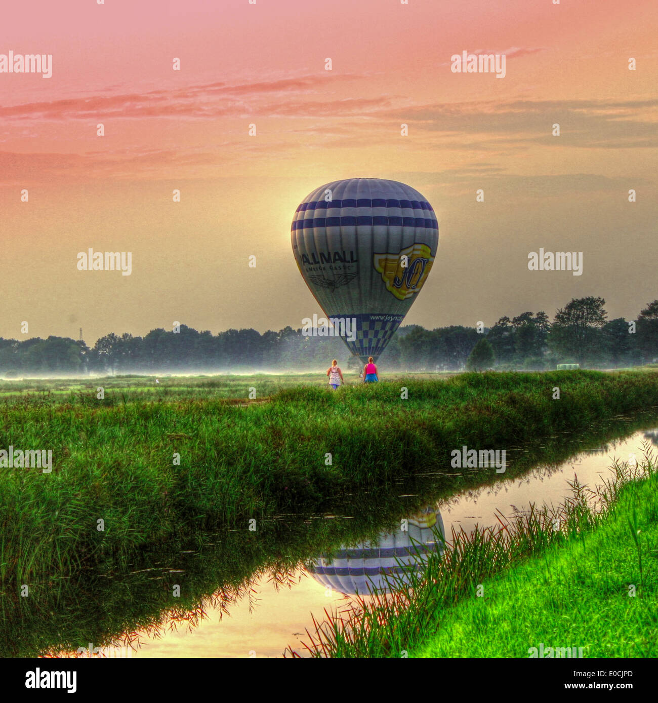 Hot air balloon just after landing in  a summer landscape in the Northern Netherlands (HDR edit) - Stock Image
