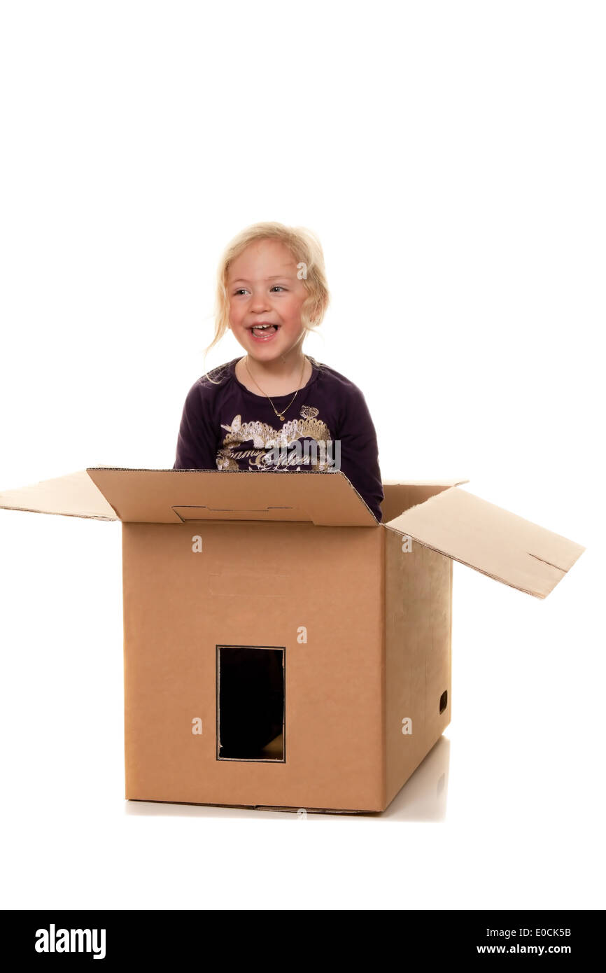 Child in move cardboard. Lies with the move in box., Kind in Umzugskarton. Liegt beim Umzug in Schachtel. - Stock Image