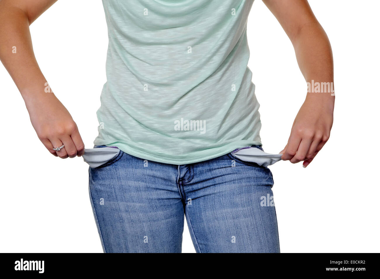 A young woman shows the empty trouser pockets of her jeans - Stock Image