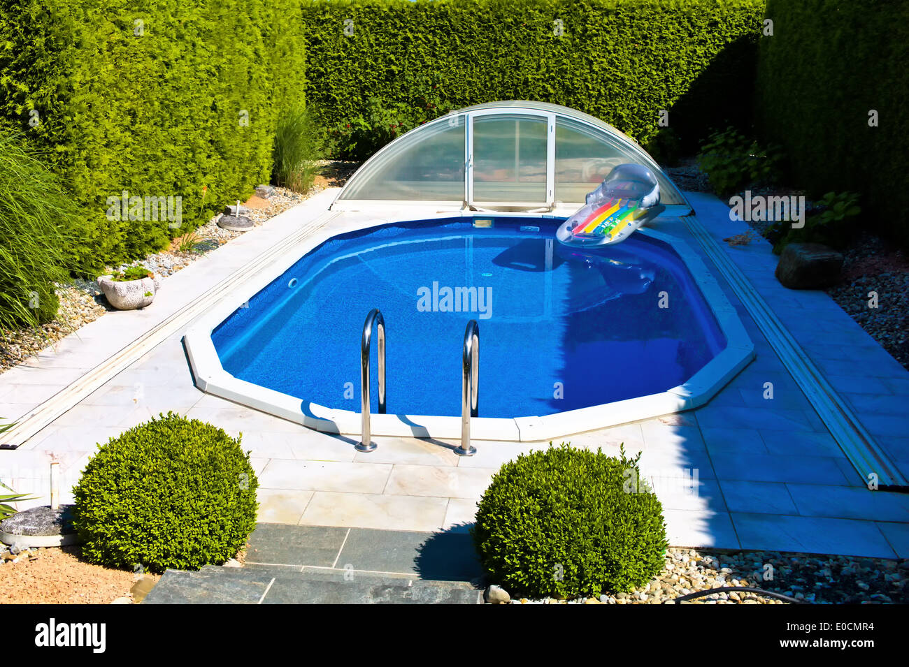 The swimming-pool of a single-family dwelling invites to Baden, Das Schwimmbad eines Einfamilienhauses laedt zum Baden ein - Stock Image