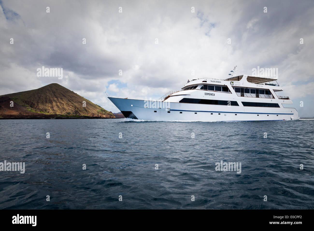 Luxury yacht under clouded sky off Bartolome Island, Galapagos, Ecuador, South America - Stock Image