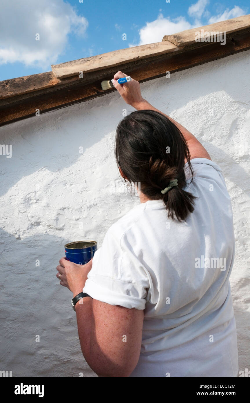 Woman weatherproofing exposed woodwork on roof terrace of a French holiday villa. - Stock Image