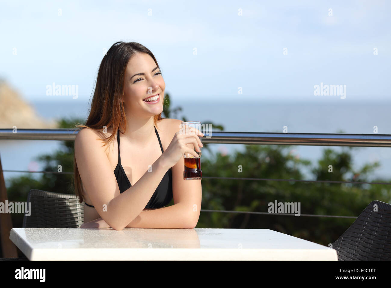 Woman on vacation drinking in a hotel terrace with the beach in the background - Stock Image