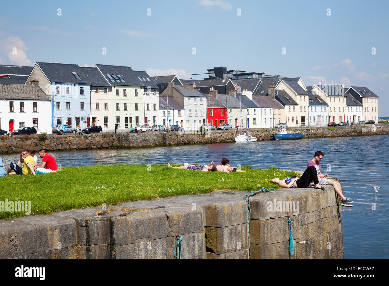 People sitting along the River Corrib in the Cladagh Area; Galway City, County Galway, Ireland - Stock Image