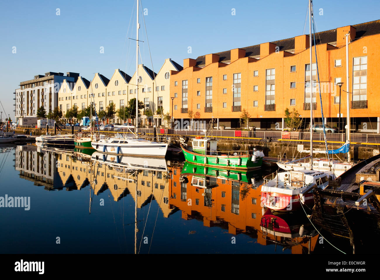 Buildings and boats reflected in tranquil water; Galway City, County Galway, Ireland - Stock Image