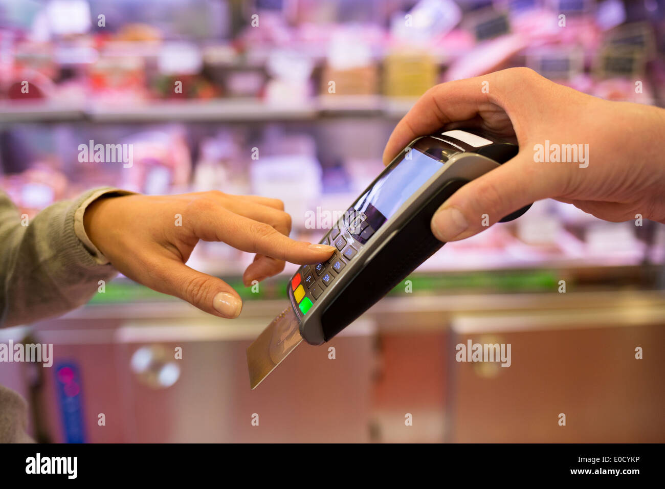 Female paying plastic card shop butcher code supermarket Stock Photo