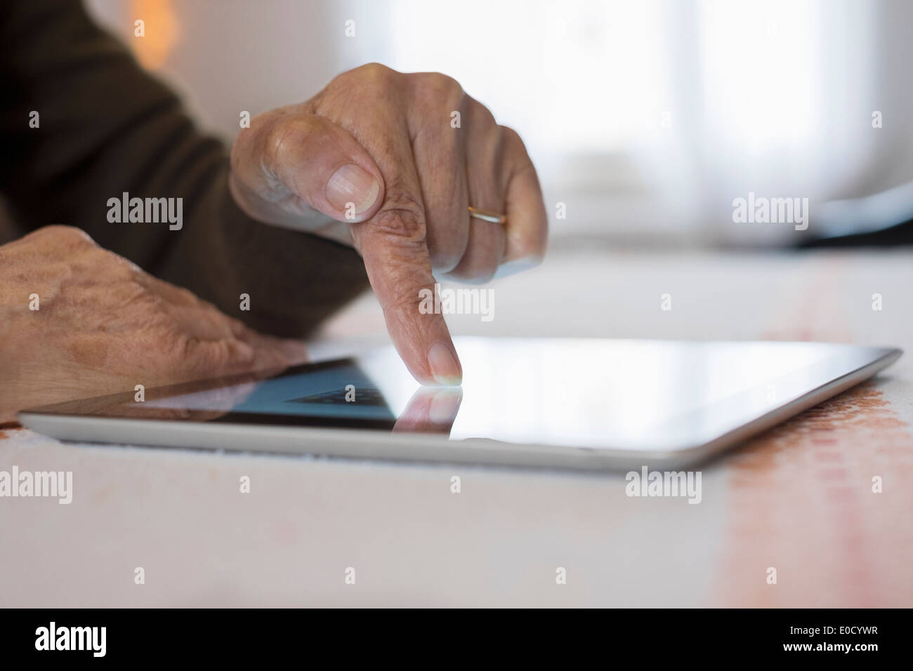 Female mature writing digital tablet indoors closeup - Stock Image