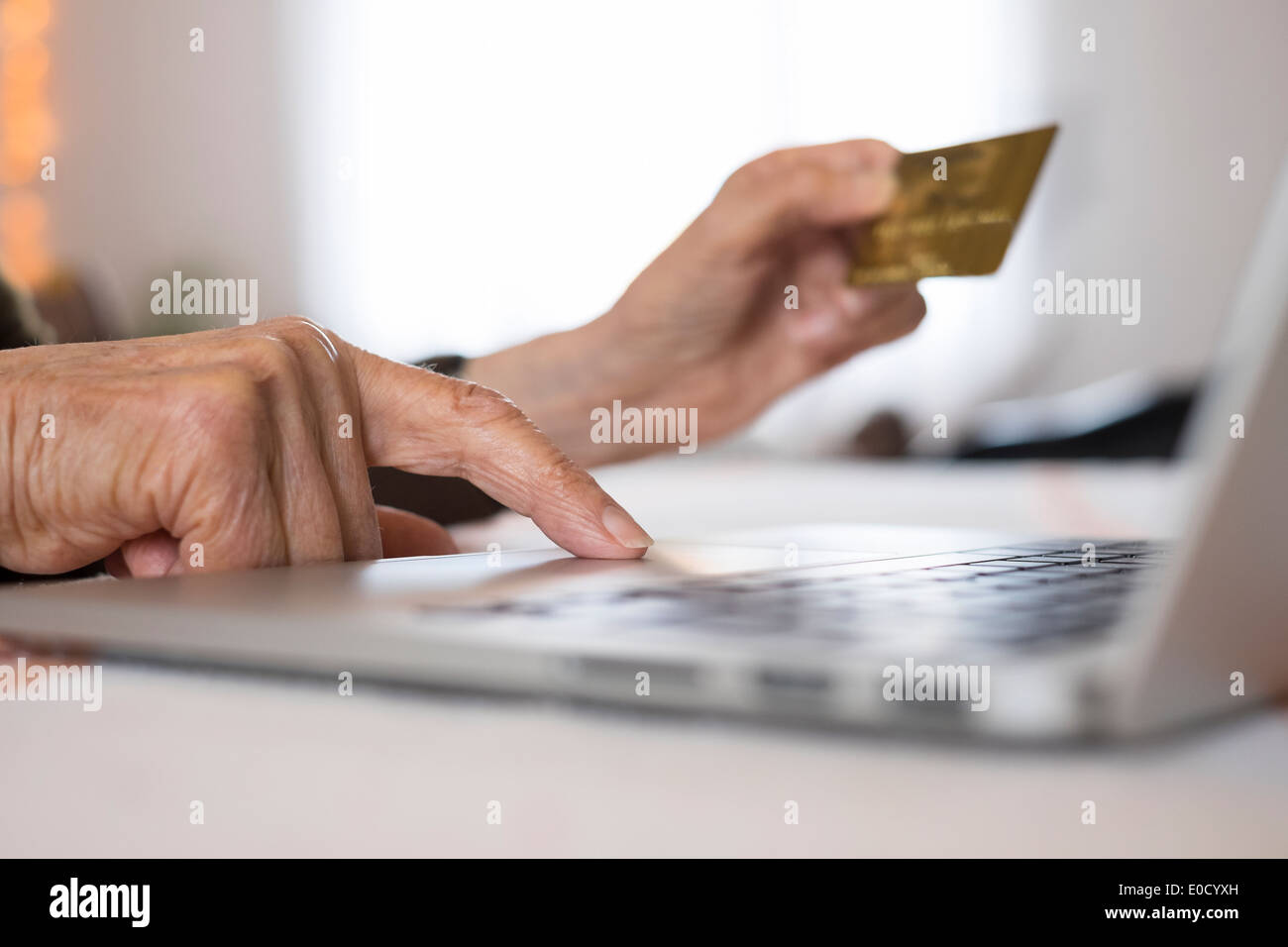 Mature female laptop closeup hands plastic card shop indoors - Stock Image