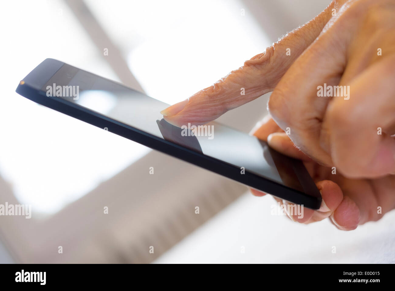 Female mature writing cell phone indoors closeup - Stock Image