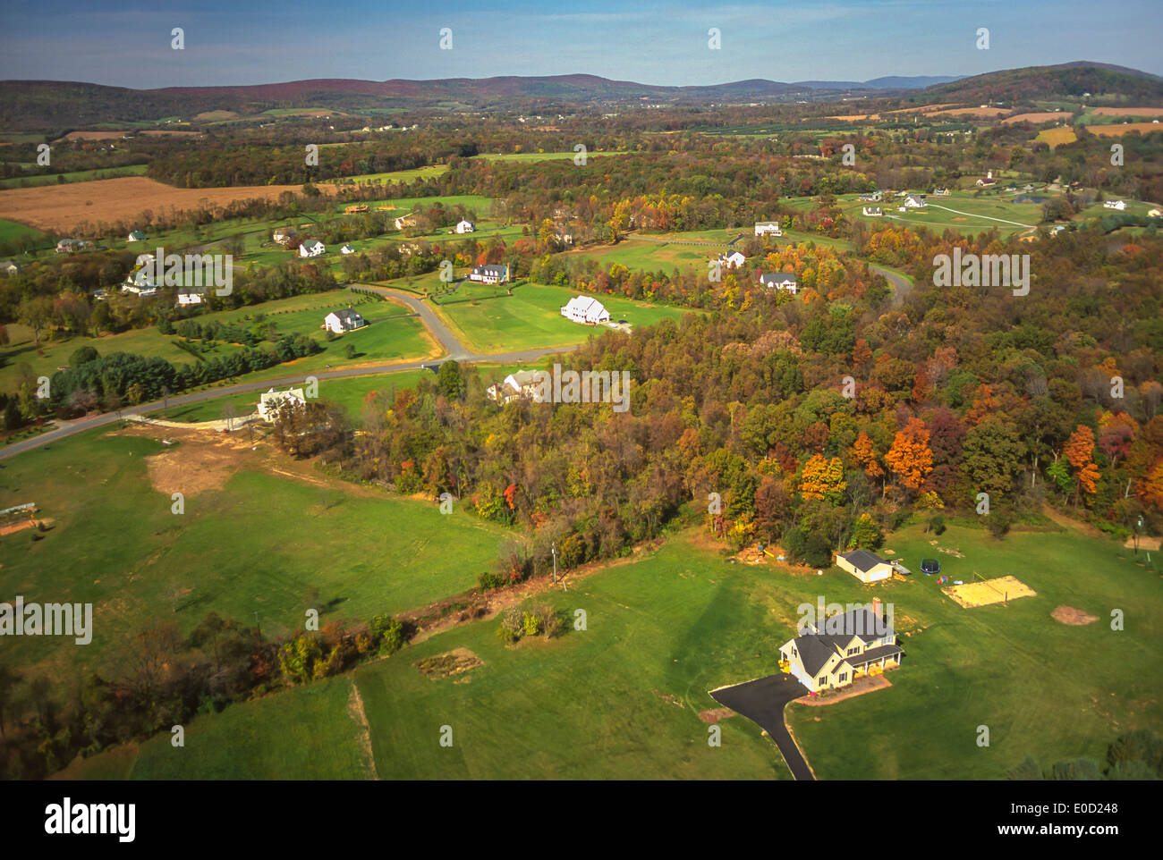 LOUDOUN COUNTY, VIRGINIA, USA - Aerial of homes on large plots of land near Blue Ridge Mountains.