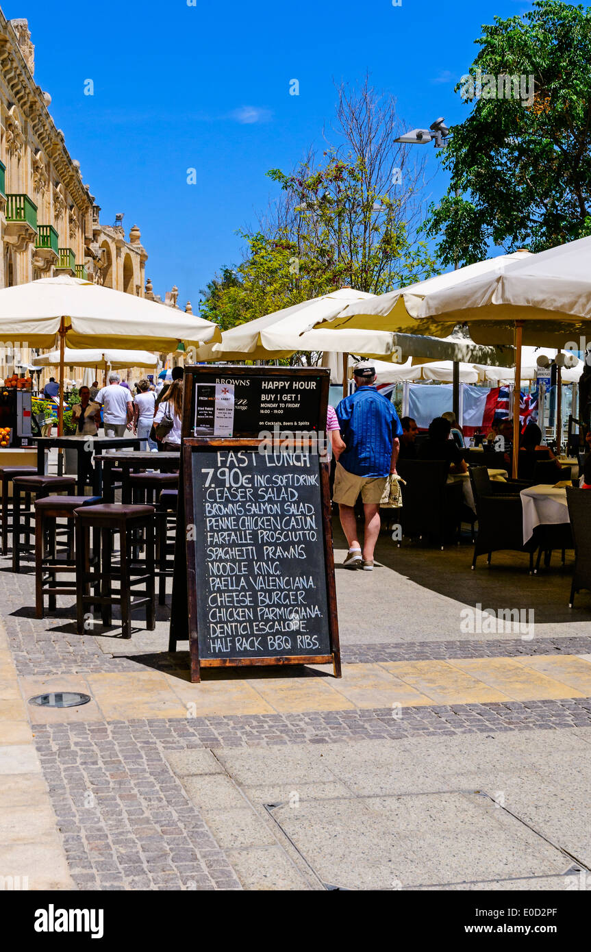 Tourists walk past a menu-board and through a typical restaurant with tables set on either side of the path at the harbour - Stock Image