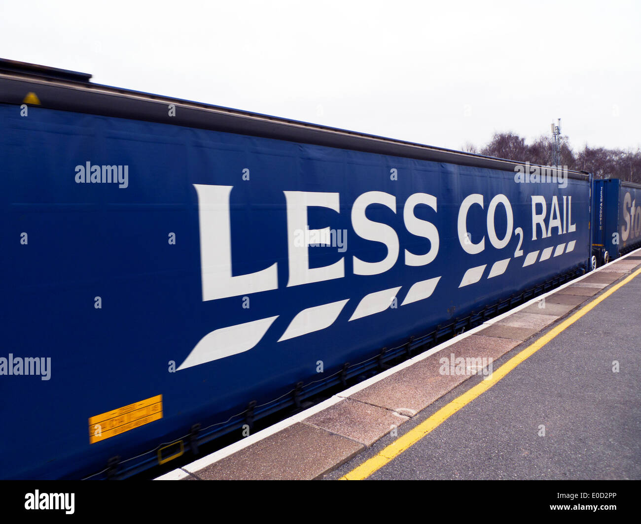 Tesco supermarket 'Less CO2 Rail' advert sign on side of goods train container  Gloucestershire England UK KATHY DEWITT - Stock Image