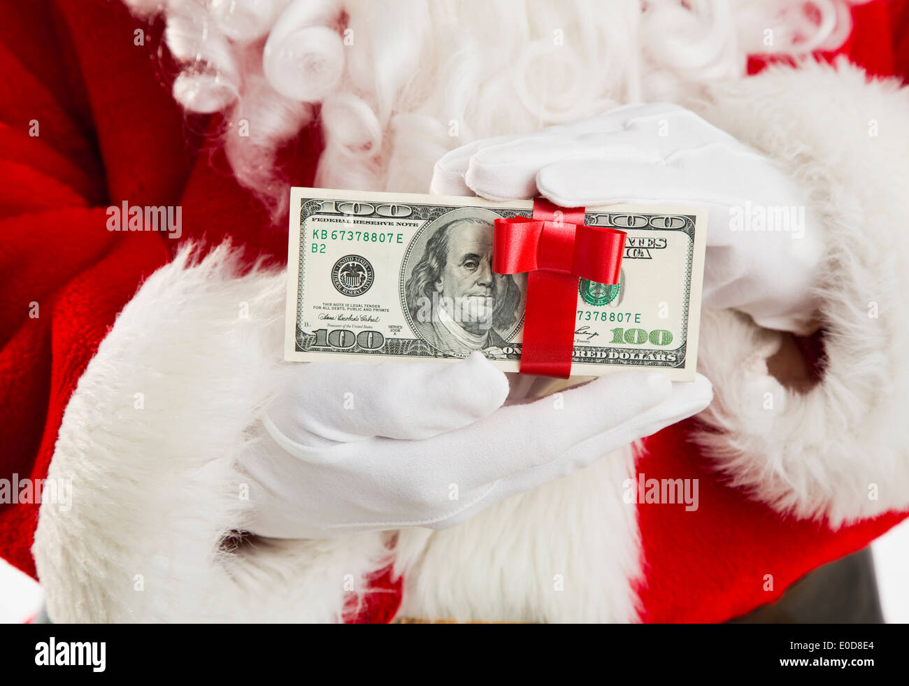 Mid section of Santa holding paper currency tied with ribbon - Stock Image