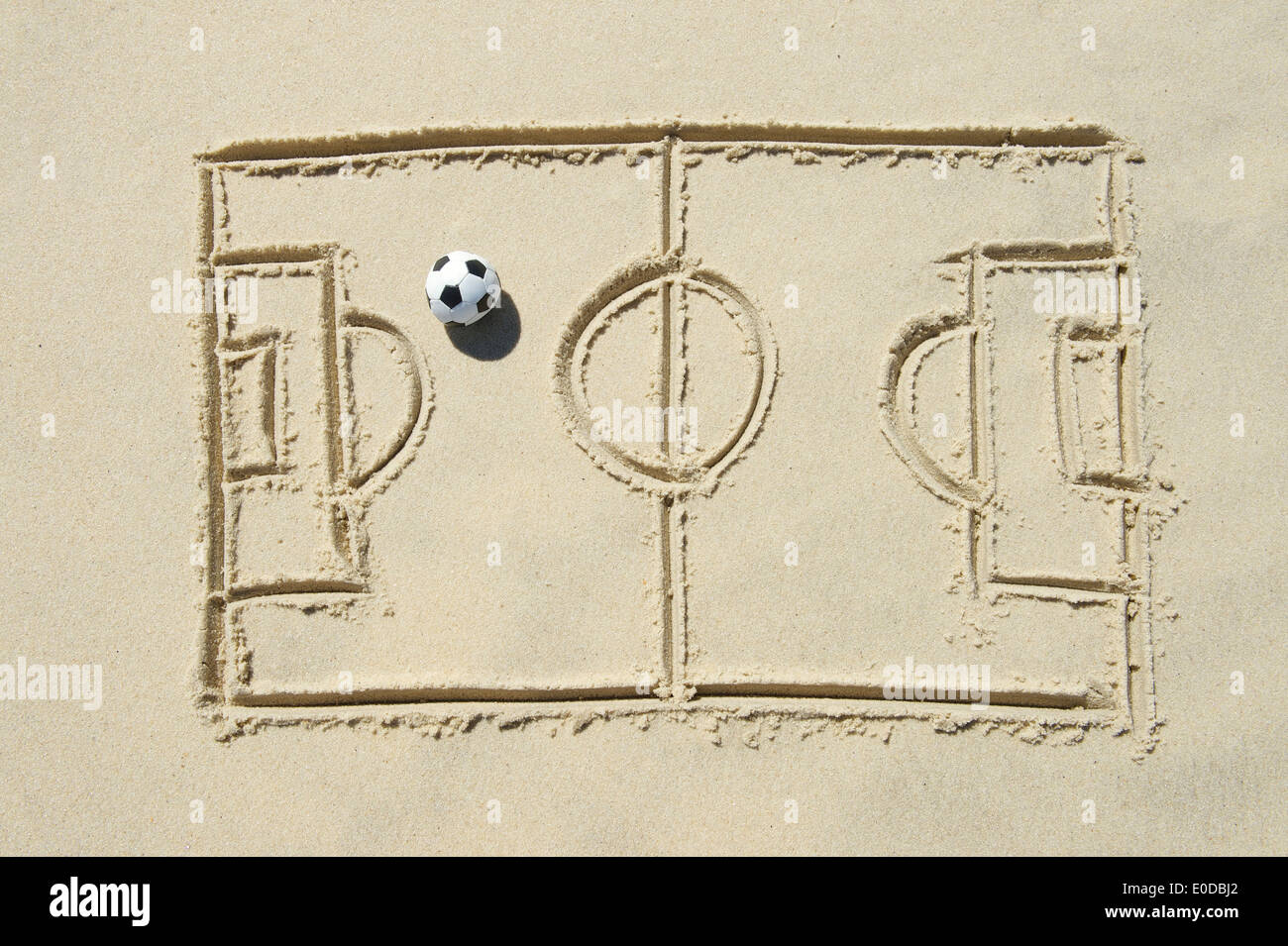 Simple line drawing of football pitch with soccer ball in sand on Brazilian beach - Stock Image