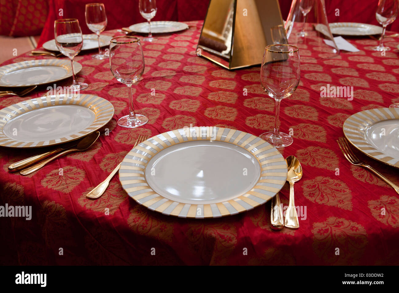 Dining table being prepped for large dinner event - Stock Image