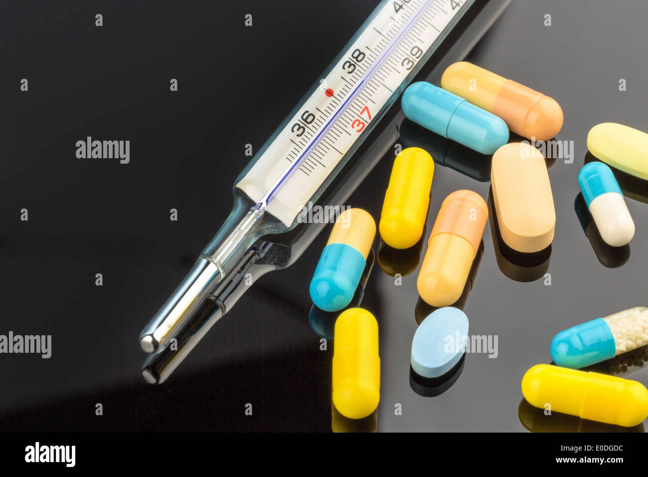 A clinical thermometer and tablets. Symbolic photo for influenza and colds, Ein Fieberthermometer und Tabletten. Symbolfoto fuer - Stock Image