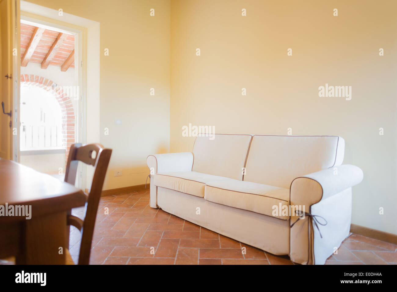A Warm An Cozy Living Room With A Cream Colored Sofa Stock Photo