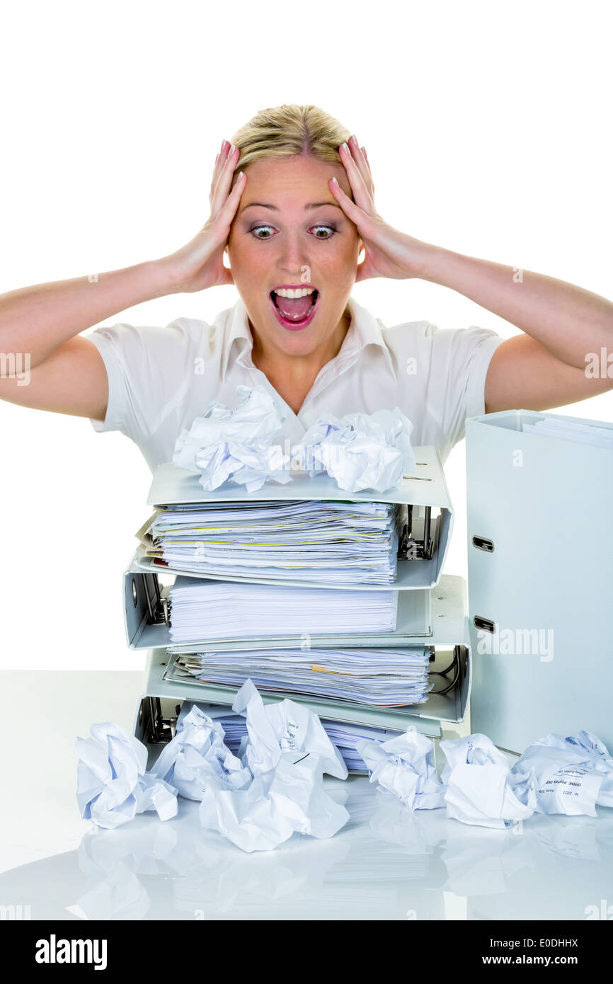 A young woman despairs in the office between many files and crumpled up paper. Symbolic photo for stress, Burnout Stock Photo