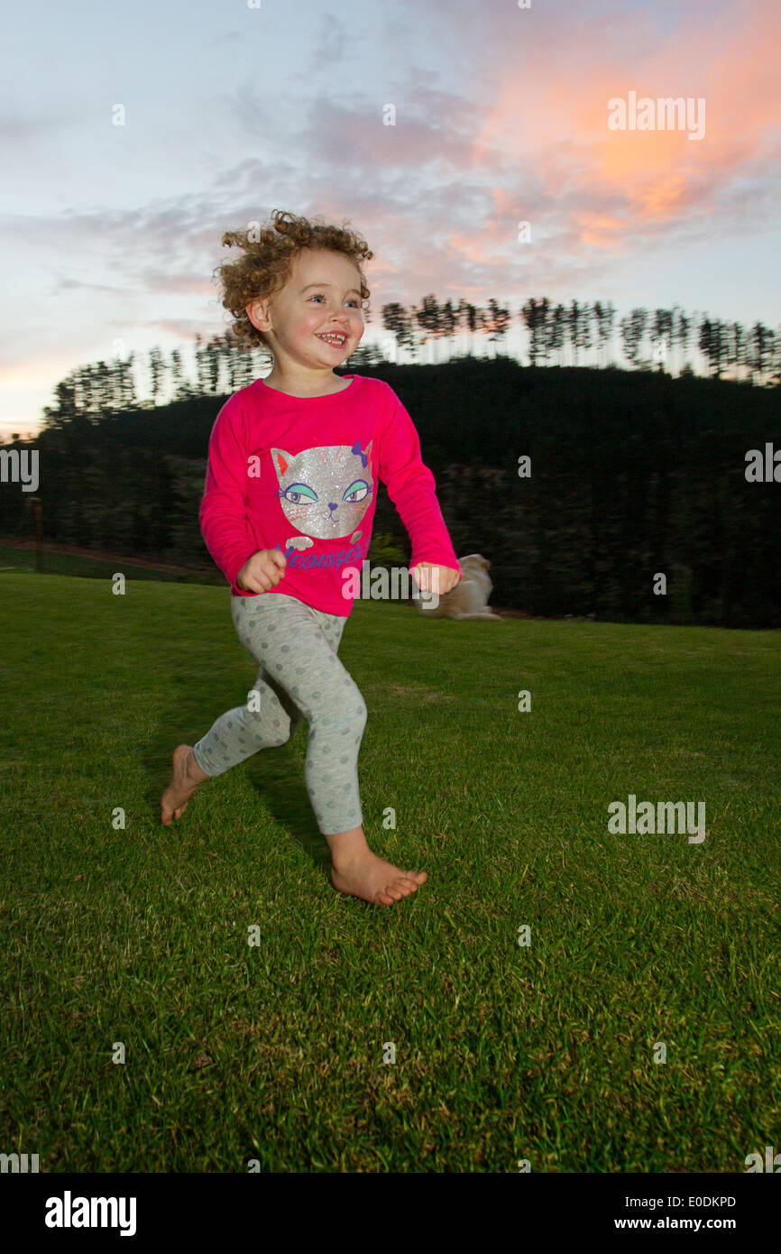 Young girl smiling and running on a farm at sunset - Stock Image