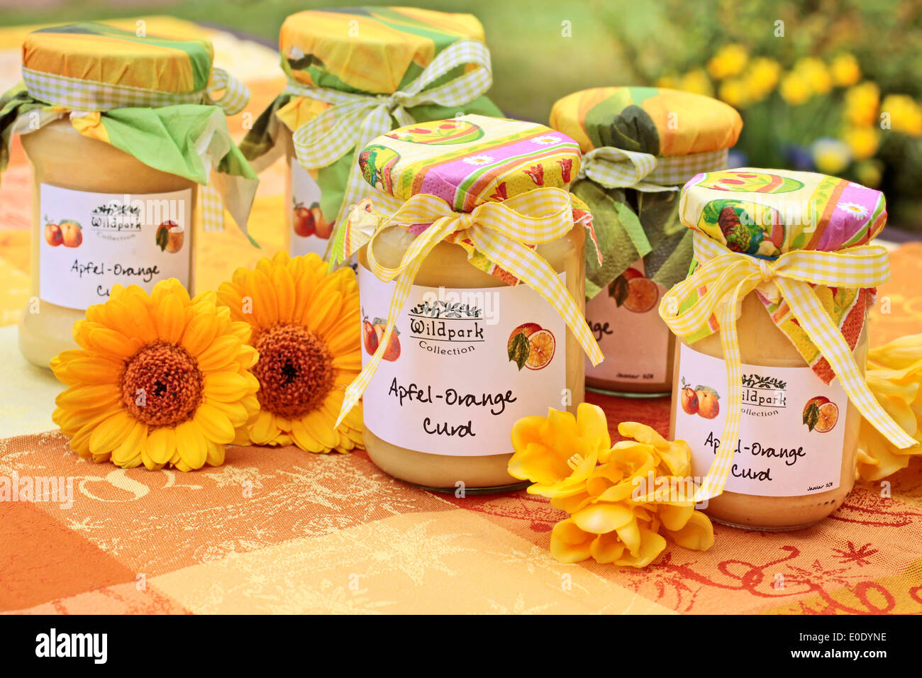 Apple-orange curd on a colorful tablecloth with flowers - Stock Image