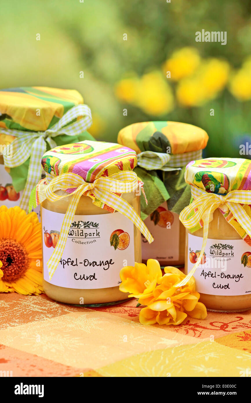 Apple-orange curd on a colorful tablecloth in the garden - Stock Image