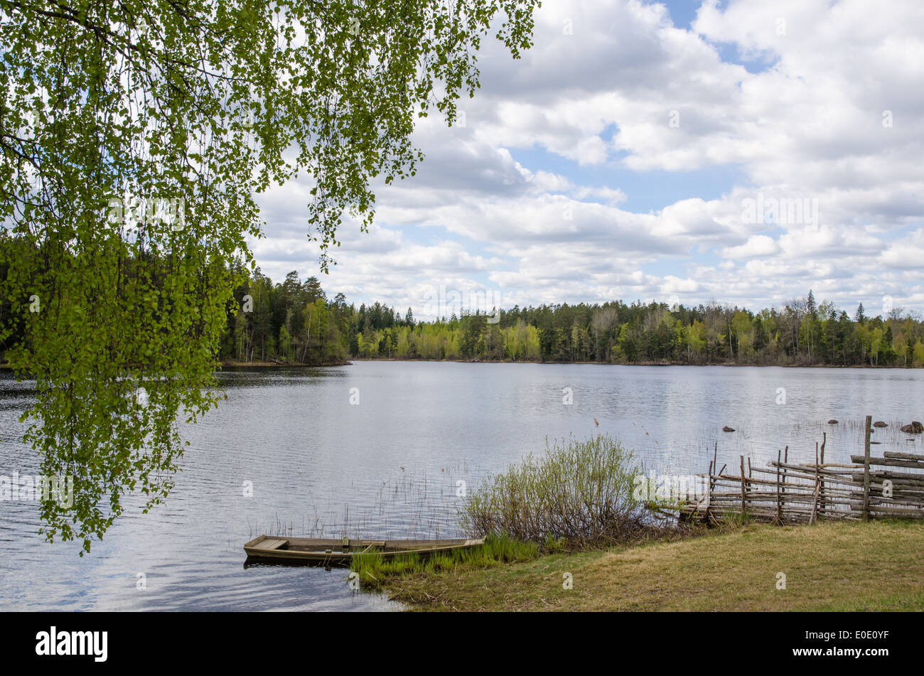 Old-fashioned lake view with a rowing boat at springtime Stock Photo
