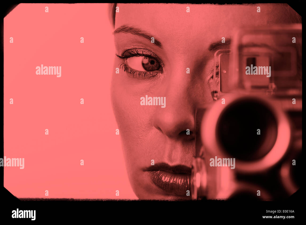 Tight crop shot on face of womanlooking through a kodak super 8 movie camera with red filter and movie film frame. - Stock Image