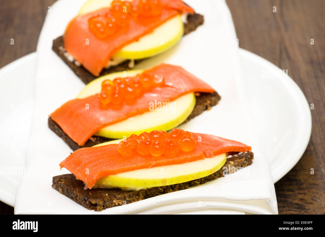 Canapes with wild salmon, caviar and apple slice - Stock Image