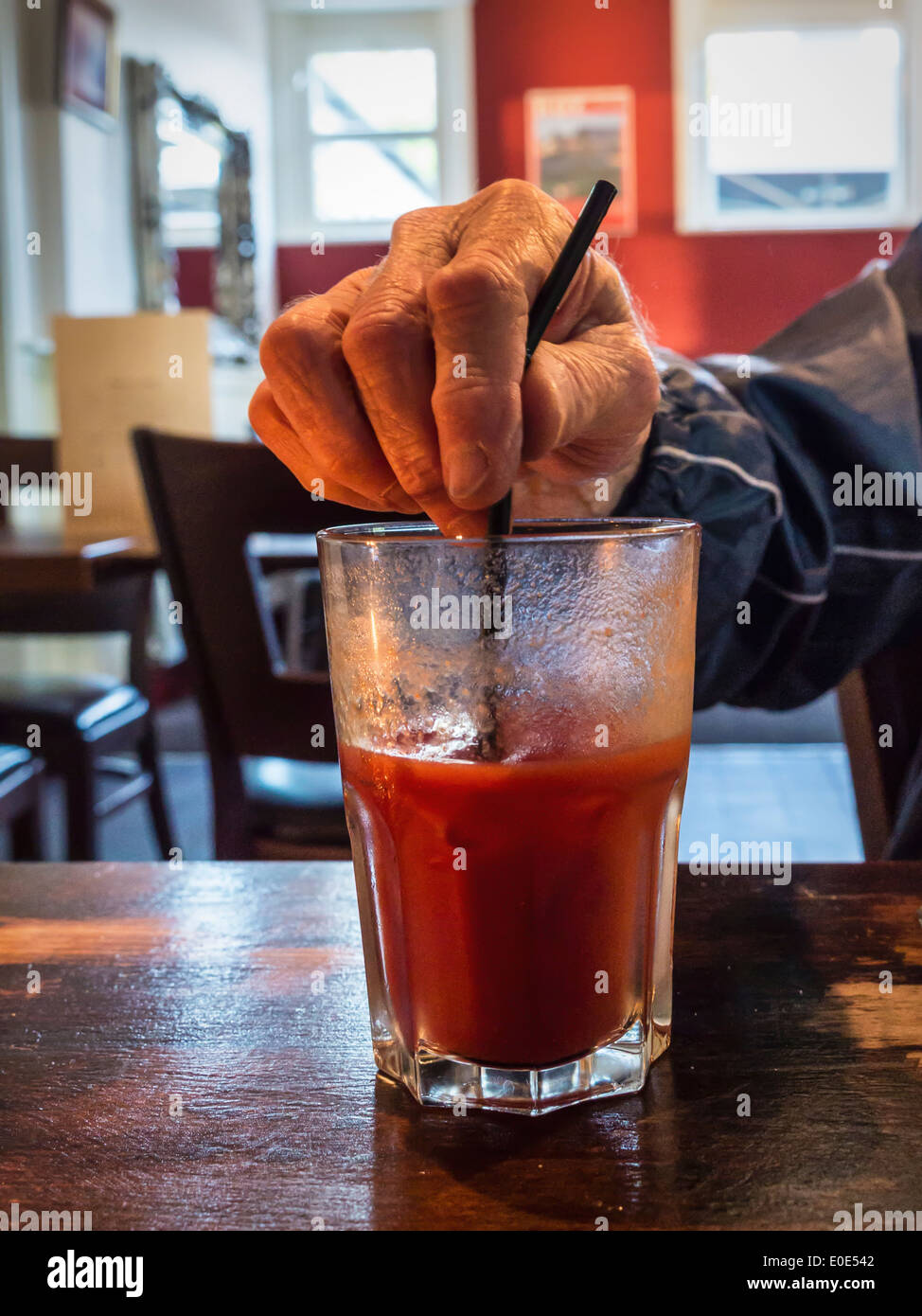 Hand stirring half full glass of tomato juice with a straw - Stock Image