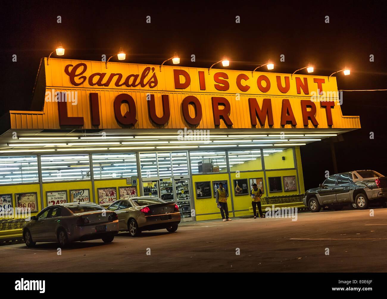 Discount liquor store at night. - Stock Image