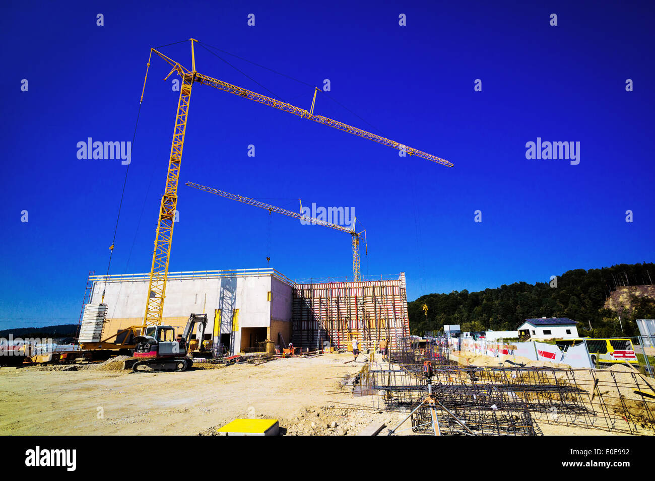 A construction crane on a building site of an industrial building. Before blue sky with text clearance, Ein Baukran auf einer Ba - Stock Image