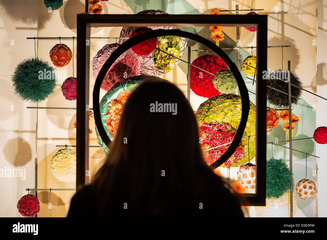 Woman admires flower art at a gallery. - Stock Image