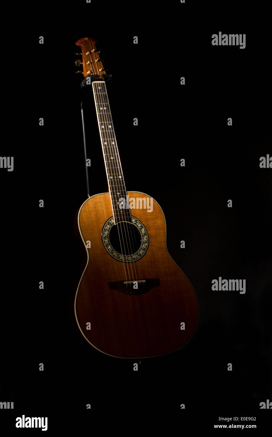 Spotlit Acoustic Guitar on a black background stringed instrument - Stock Image
