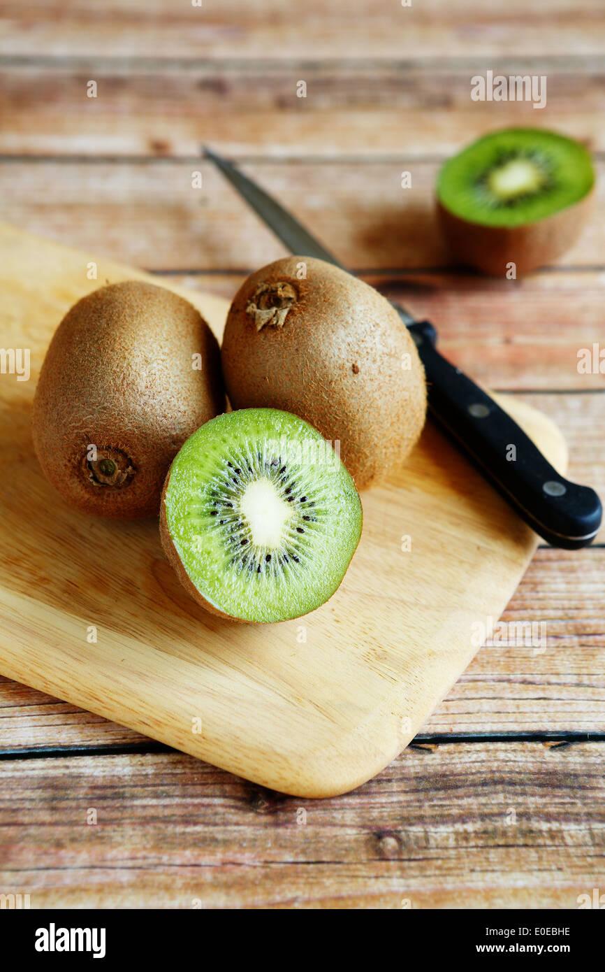 fresh kiwi on cutting board and knife - Stock Image