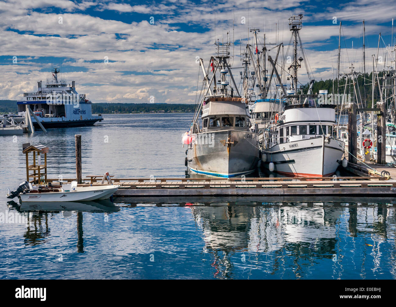 Fishing boats at marina, ferry in dist, going to Campbell River from Quathiaski Cove on Quadra Island, British Columbia, Stock Photo