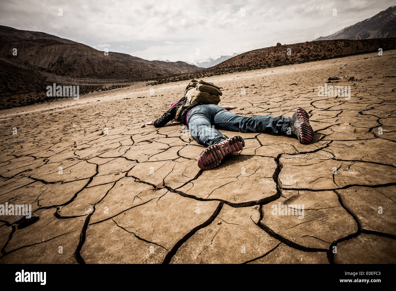 traveller lays on the dried ground - Stock Image