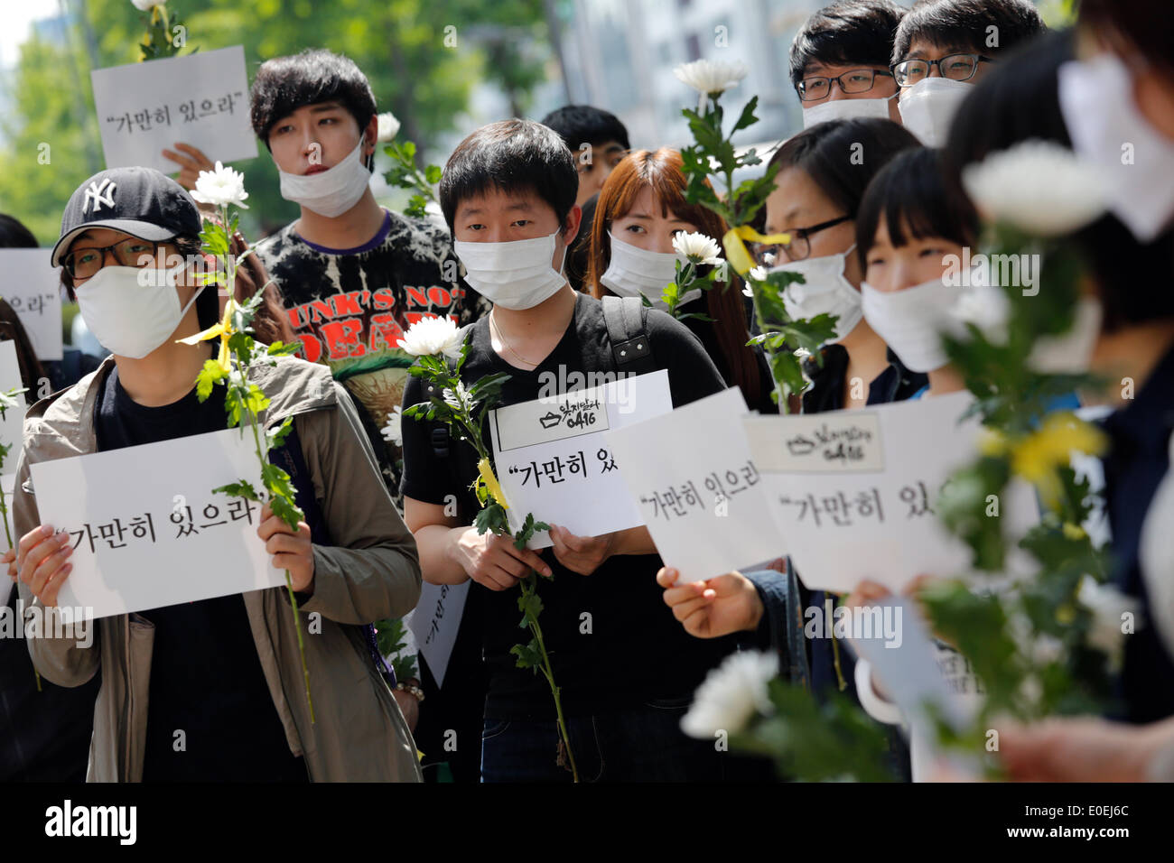 Seoul, South Korea. 10th May 2014. People hold signs and flowers during their 'Stay Still' silent march against what they insist, lax response of President Park Geun-hye's government after the Sewol ferry was sunken in waters off the southwestern island of Jindo on April 16, 2014, on the street, Seoul, South Korea, on Saturday May 10, 2014. Signs read,'Stay still', pasquinading captain of Sewol, who was broadcasting a message for passengers to wait until further notice, when the ferry was sinking, according to local media. - Stock Image