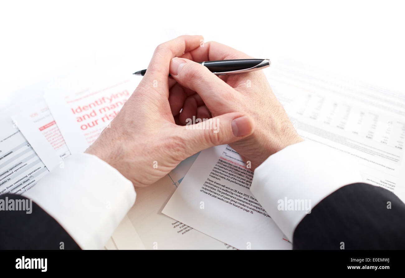 Looking down on the hands of a businessman studying contracts and risk management papers. - Stock Image
