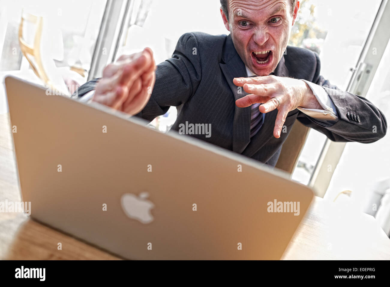 An angry businessman karate chops his laptop in frustration. - Stock Image