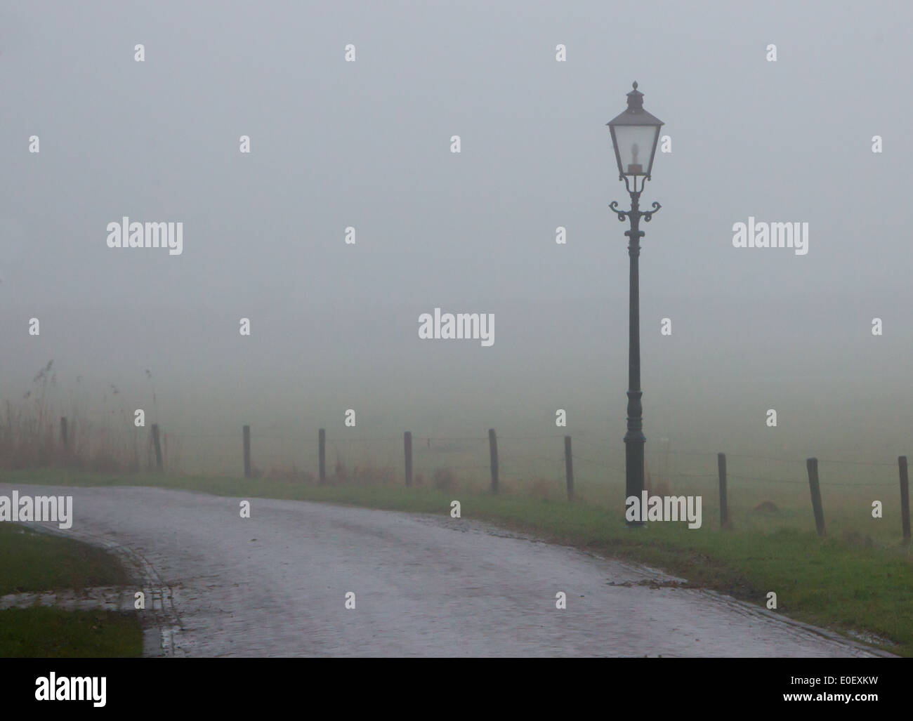Lantern at a misty road, Ameland - Holland Stock Photo