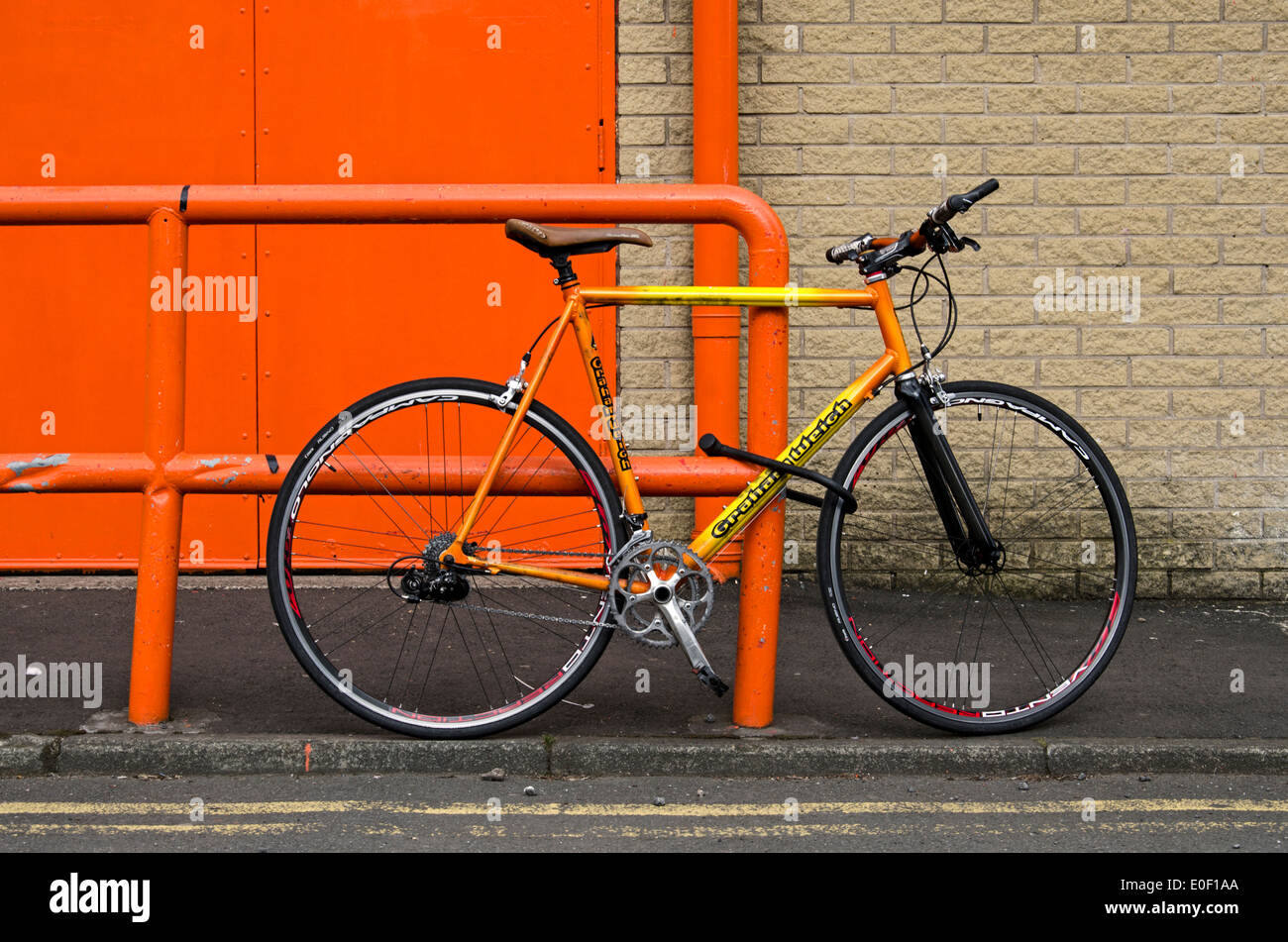An orange and yellow coloured bicycle secured to an orange rail with an orange door in the background. - Stock Image