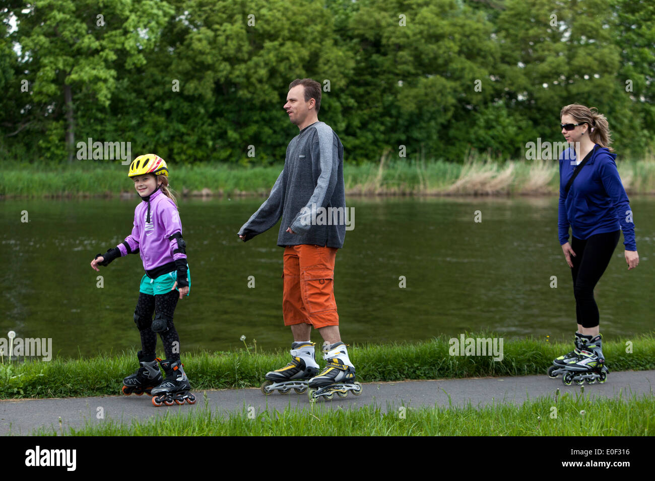 People on the bike trail, roller skating family - Stock Image
