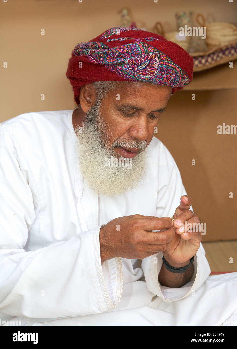MUSCAT, OMAN - FEBRUARY 1, 2008: A bearded Omani craftsman, wearing a traditional muzzar (headcloth), at work in Muscat, Oman. - Stock Image