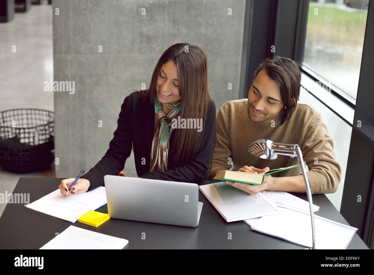 Young students taking notes from reference books for study. Young man and woman sitting at table with books and laptop. - Stock Image