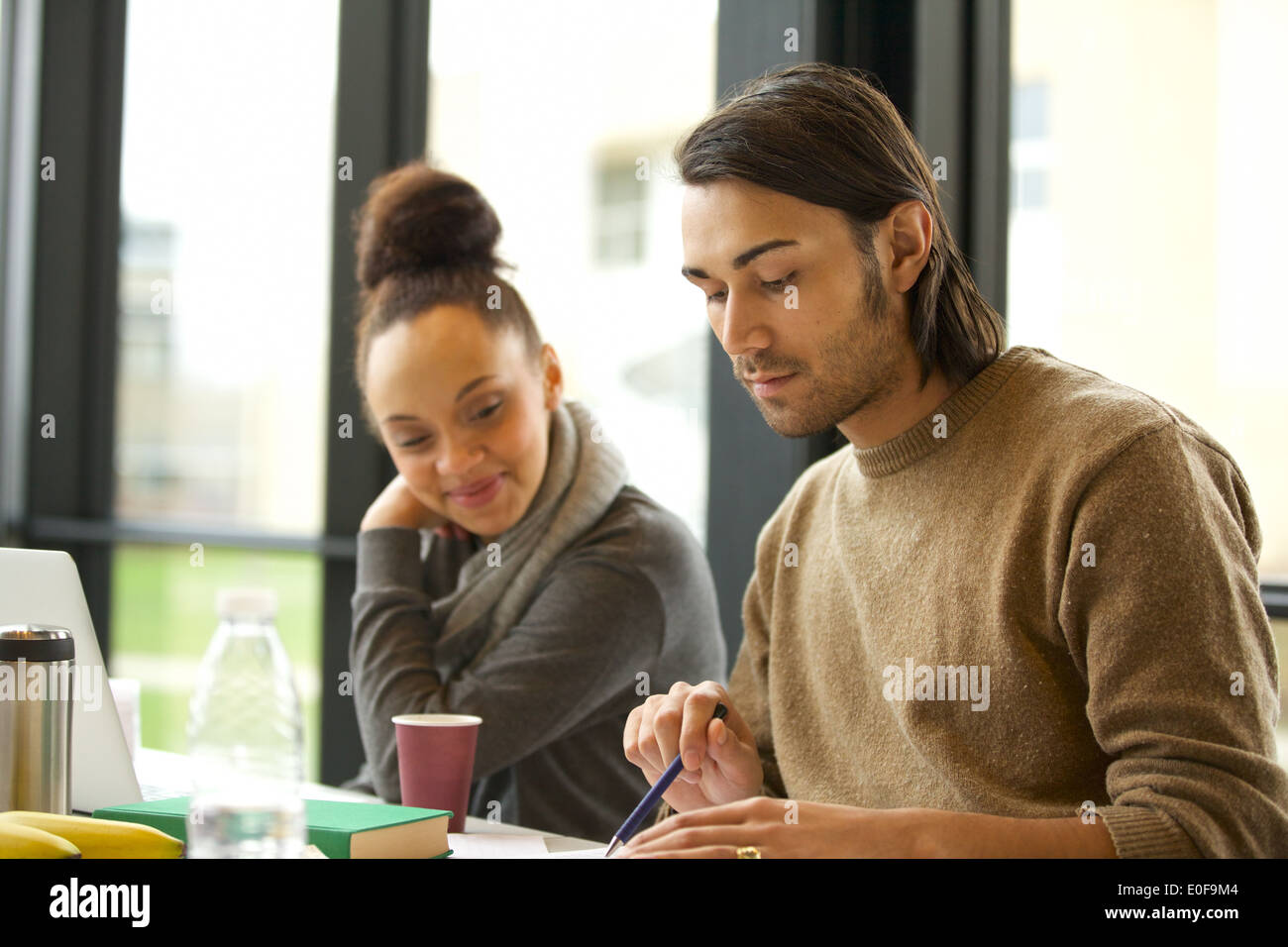 Young man studying hard with woman sitting by. University students preparing for final exams. - Stock Image